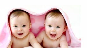 Cute twins baby girls under the pink blacket